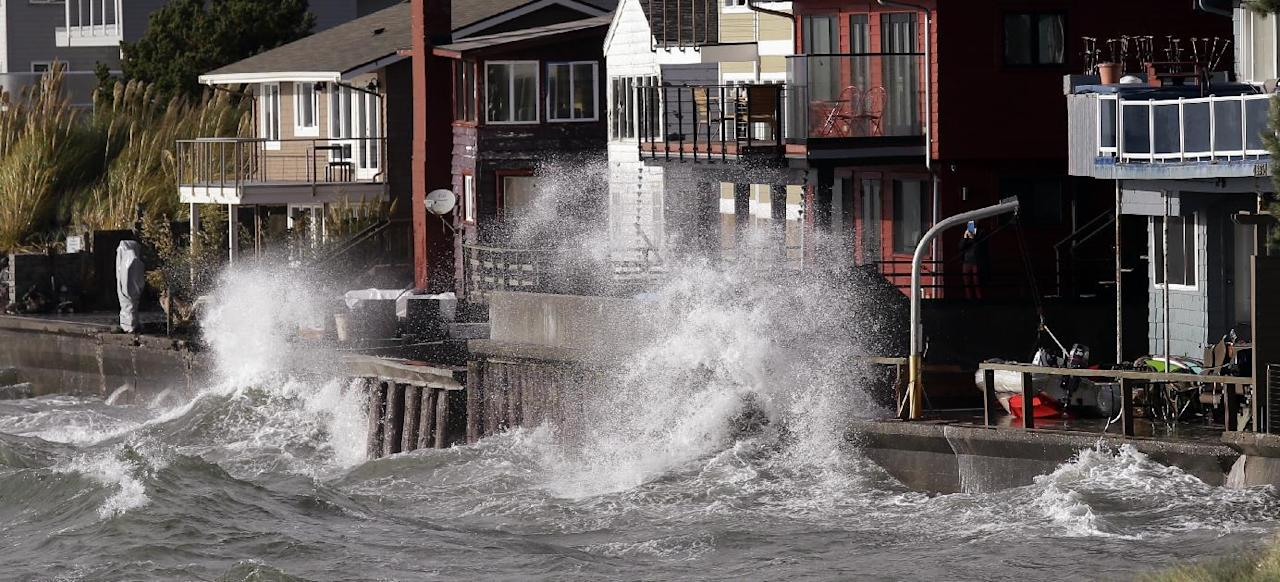 Waves batter a seawall as water hits adjacent homes Friday, Oct. 14, 2016, in Seattle. A tornado struck an Oregon beach town Friday, sending debris flying and toppling power lines and trees as strong winds and heavy rain walloped the Pacific Northwest. Thousands of people were without power as utility crews in the region prepared for what's expected to be an even rougher storm on Saturday. (AP Photo/Elaine Thompson)