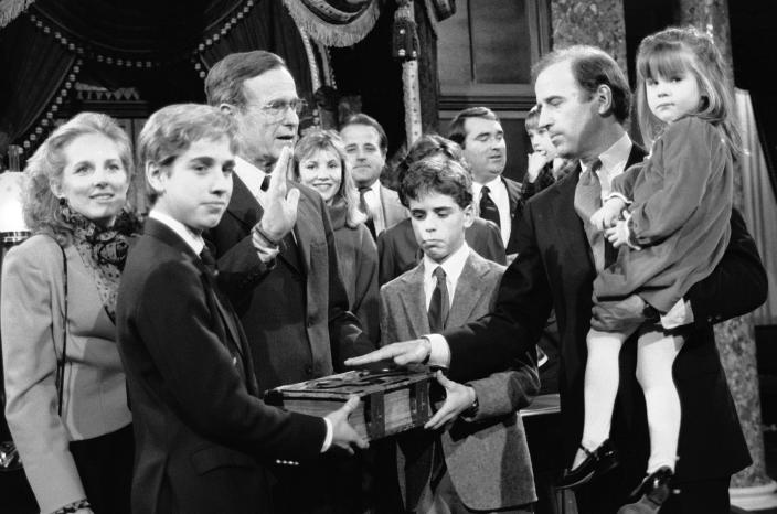 FILE - In this Jan. 3, 1985 file photo, Sen. Joe Biden, D-Del., holds his daughter Ashley while taking a mock oath of office from Vice President George Bush during a ceremony on Capitol Hill, in Washington. Biden's sons Beau and Hunt hold the bible during the ceremony. (AP Photo/Lana Harris, File)