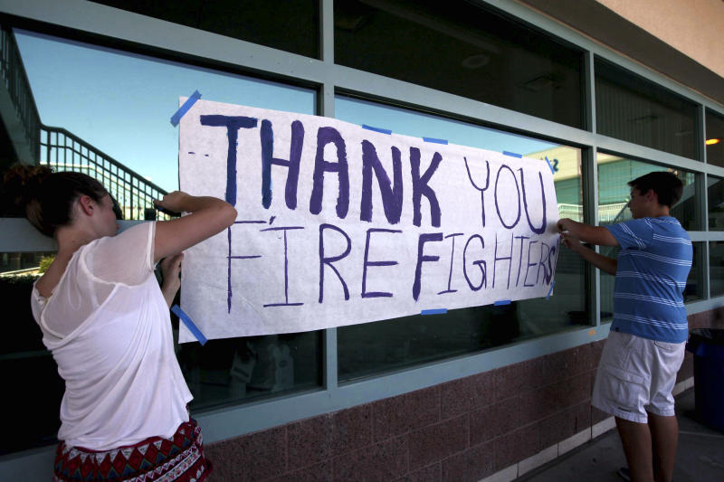 Centennial High School student council members Bridgett Bevilacqua, left, and Dylan Sacenti, both 17-year-old seniors, tape up a sign of support for firefighters at Centennial High School, the Carpenter 1 fire command center, in Las Vegas on Monday, July 8, 2013. The wildfire, which encompasses thousands of acres, began last Monday. (AP Photo/Las Vegas Review-Journal, Jessica Ebelhar) LOCAL TV OUT; LOCAL INTERNET OUT; LAS VEGAS SUN OUT
