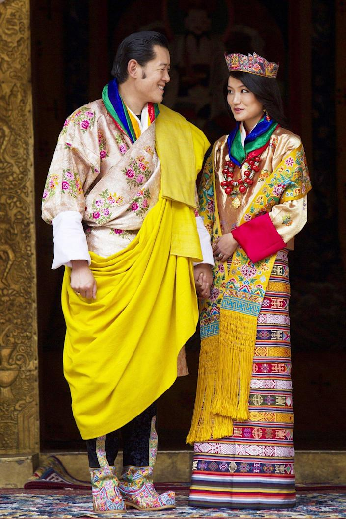 His majesty King Jigme Khesar Namgyel Wangchuck, 31, holds his Raven crown as he and the Queen Jetsun Pema, 21, walk out after their marriage ceremony is completed on October 13, 2011 in Punakha, Bhutan.