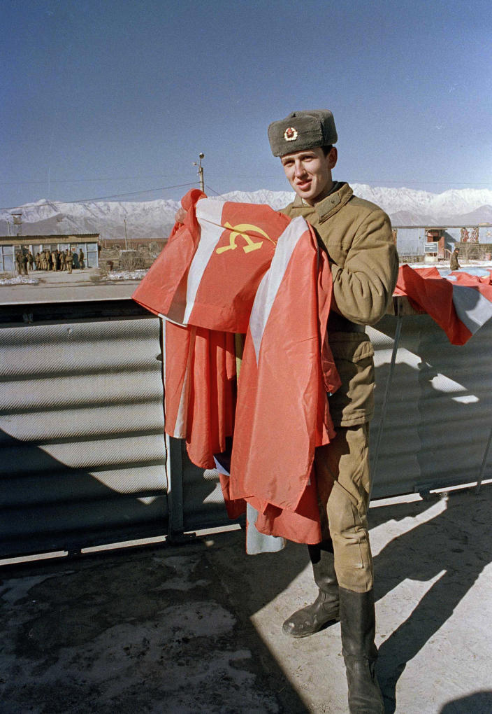 FILE - In this Jan. 25, 1989 file photo, a Soviet soldier folds the Soviet flag at Kabul air base as the Soviet military prepare for their final withdrawal from war-torn Afghanistan. A UN-brokered accord set a Feb. 15 pullout date. Afghanistan is marking the 31st anniversary of the Soviet Union's last soldier leaving the country, Saturday, Feb. 15, 2020. This year's anniversary comes as the United States negotiates its own exit after 18 years of war, America's longest. (AP Photo/Liu Heung Shing)