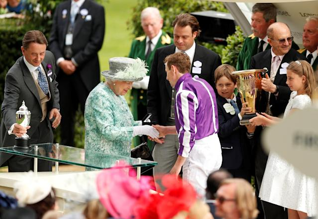 Horse Racing - Royal Ascot - Ascot Racecourse, Ascot, Britain - June 23, 2018 Britain's Queen Elizabeth presents a trophy for the 4.20 Diamond Jubilee Stakes to Ryan Moore, who rode the winner Merchant Navy Action Images via Reuters/Andrew Boyers