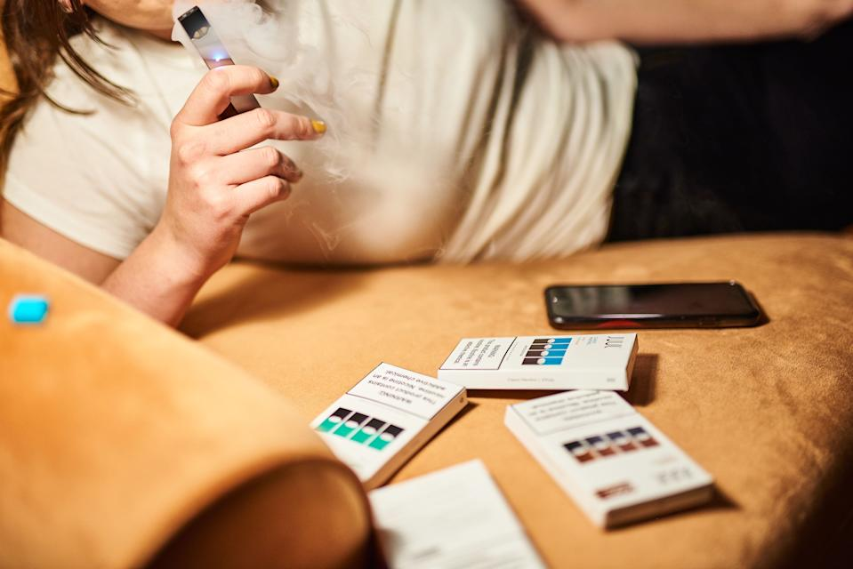 A person smokes a Juul Labs Inc. e-cigarette in this arranged photograph taken in the Brooklyn Borough of New York, U.S., on Thursday, Dec. 20, 2018. Altria Group's plan to take a $12.8 billionstakein Juul Labs could be destroying value, Citigroup analysts write in a note downgrading the stock to a sell from neutral. Photographer: Gabby Jones/Bloomberg via Getty Images
