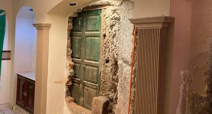 A door is pictured behind a knocked down wall in a Mexican home.