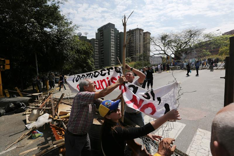 """Demonstrators set up a banner that reads in Spanish """"Democracy, Yes. Communism, No"""", as they set up a barricade in La Boyera neighborhood in Caracas, Venezuela, Thursday, Feb. 20, 2014. Violence is heating up in Venezuela as an opposition leader Leopoldo Lopez, faces criminal charges for organizing a rally that set off a deadly week of turmoil in anti-government protests in Caracas and other cities where demonstrators and government forces clashed leaving several dead and scores of wounded. (AP Photo/Fernando Llano)"""