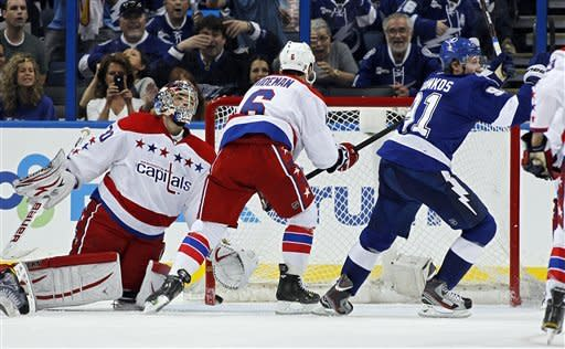 Tampa Bay Lightning's Steven Stamkos, right, celebrates his goal against Washington Capitals' Michal Neuvirth, left, of the Czech Republic, and Dennis Wideman during the third period of an NHL hockey game Monday, April 2, 2012, in Tampa, Fla. The Lightning won 4-2. (AP Photo/Mike Carlson)