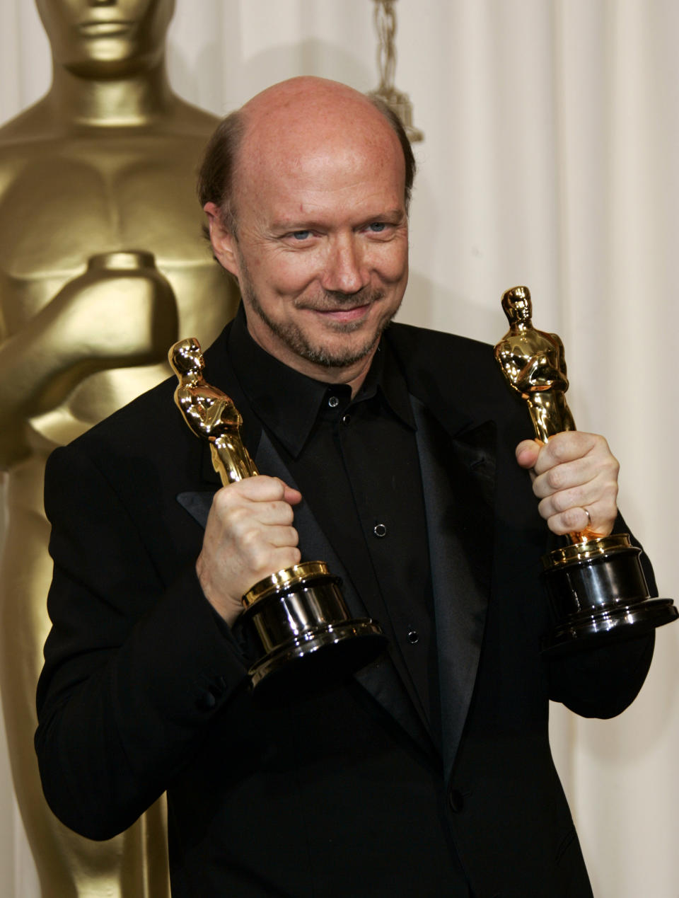Director Paul Haggis poses with the two Oscars he won for best motion picture of the year and best original screenplay at the 78th Academy Awards Sunday, March 5, 2006, in Los Angeles. (AP Photo/Kevork Djansezian)