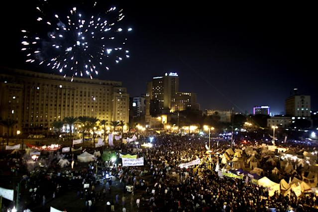 Fireworks burst over Tahrir Square as protesters gather in Cairo, Egypt, Tuesday, Dec. 4, 2012. A protest by tens of thousands of Egyptians outside the presidential palace in Cairo turned violent on Tuesday as tensions grew over Islamist President Mohammed Morsi's seizure of nearly unrestricted powers Thousands of protesters also gathered in Cairo's downtown Tahrir Square, miles away from the palace, to join several hundred who have been camping out there for nearly two weeks. (AP Photo/Maya Alleruzzo)