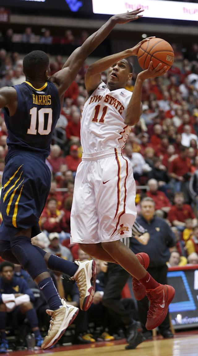 Iowa State guard Monte Morris goes up for a shot over West Virginia guard Eron Harris during the first half of an NCAA college basketball game in Ames, Iowa, Wednesday, Feb. 26, 2014. (AP Photo/Justin Hayworth)