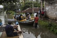 Stranded Sri Lankans travel in a boat in an inundated street following heavy rainfall in Malwana, on the out skirts of Colombo, Sri Lanka, Saturday, June 5, 2021. Flash floods and mudslides triggered by heavy rains in Sri Lanka have killed at least four people and left seven missing, while more than 5,000 are displaced, officials said Saturday. Rains have been pounding six districts of the Indian Ocean island nation since Thursday night, and many houses, paddy fields and roads have been inundated, blocking traffic. (AP Photo/Eranga Jayawardena)