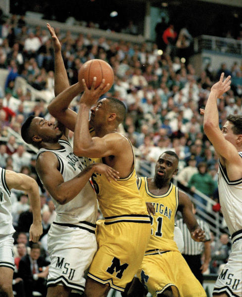 FILE - In this Feb. 3, 1993 file photo, Michigan's Juwan Howard, right, pushes against Michigan State's Dwayne Stephens as he goes up for a shot during the first half at Breslin Center in East Lansing, Mich. Howard will make his coaching debut in a heated rivalry when No. 12 Michigan plays at No. 14 Michigan State on Sunday, Jan. 5, 2020.(AP Photo/Lennox McLendon, File)