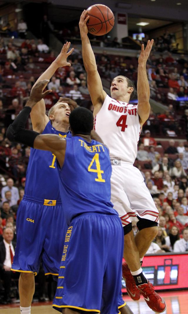 Ohio State's Aaron Craft (4) goes up to shoot against Delaware's Kyle Anderson, back left, and Jarvis Threatt (4) during the second half of an NCAA college basketball game in Columbus, Ohio, Wednesday, Dec. 18, 2013. Ohio State won 76-64. ( AP Photo/Paul Vernon)