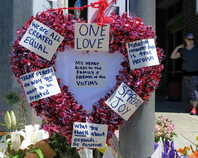 <p>A heart-shaped wreath covered with positive messages hangs on a traffic light pole at a memorial for two bystanders who were stabbed to death Friday, while trying to stop a man who was yelling anti-Muslim slurs and acting aggressively toward two young women, including one wearing a Muslim head covering, on a light-trail train in Portland, Ore, Saturday, May 27, 2017. (AP Photo/Gillian Flaccus) </p>