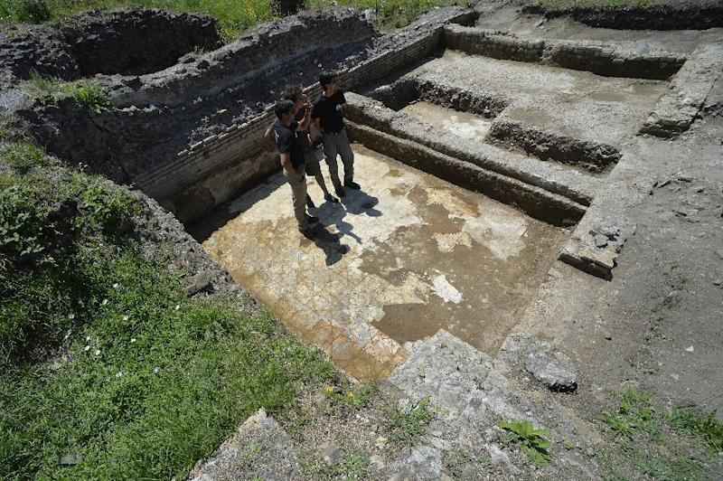 Darius Arya (L), in charge of the excavation for the American Institute for Roman Culture, presents a marble floor as part of the last discoveries at the Parco dei Ravennati excavation site in Ostia Antica on July 17, 2014 (AFP Photo/Andreas Solaro )