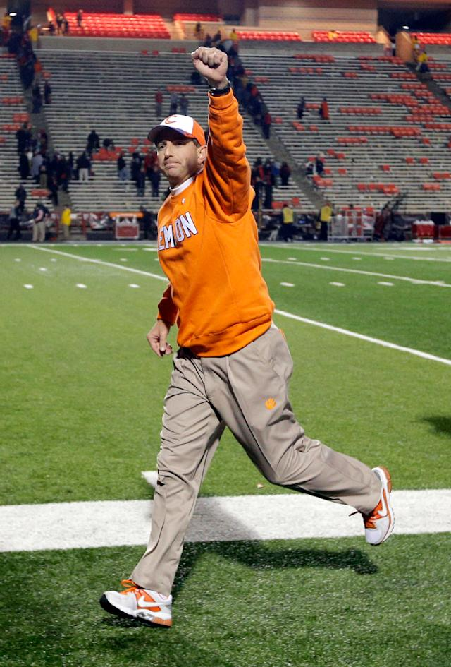 FILE - In this Oct. 26, 2013, file photo, Clemson head coach Dabo Swinney acknowledges fans as he runs off the field after an NCAA college football game against Maryland in College Park, Md. Swinney received a new, eight-year contract and a raise that increased his total pay for next season to $3.15 million. (AP Photo/Patrick Semansky, File)