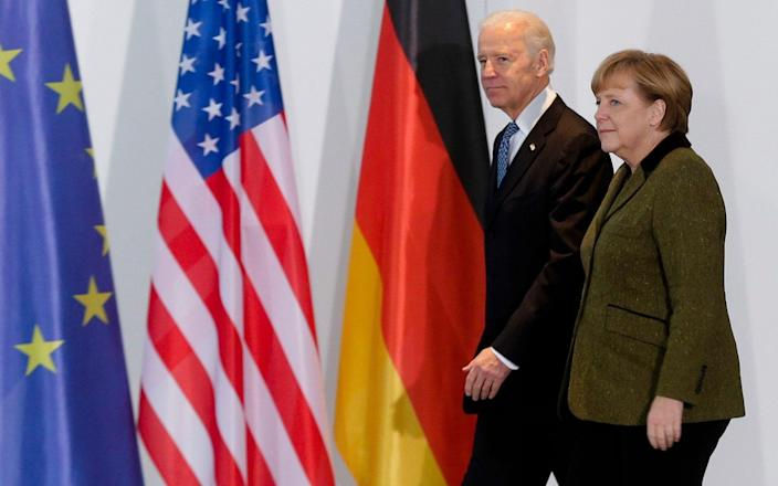 Mr Biden with Angela Merkel in 2013. The President-elect has the support of Germans, according to a new poll - AP