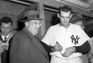FILE - In this Oct. 8, 1956, file photo, New York Yankees pitcher Don Larsen signs a baseball for Brooklyn Dodgers manager Walter O'Malley in the dressing room after Larsen pitched a perfect game against the Dodgers during Game 5 of the World Series at Yankee Stadium in New York. Larsen, the journeyman pitcher who reached the heights of baseball glory in 1956 for the Yankees when he threw a perfect game and the only no-hitter in World Series history, died Wednesday night, Jan. 1, 2020. He was 90. (AP Photo/File)