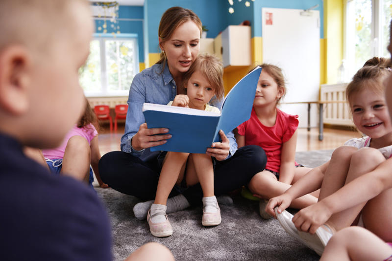 Kids and teacher reading a book together in the preschool