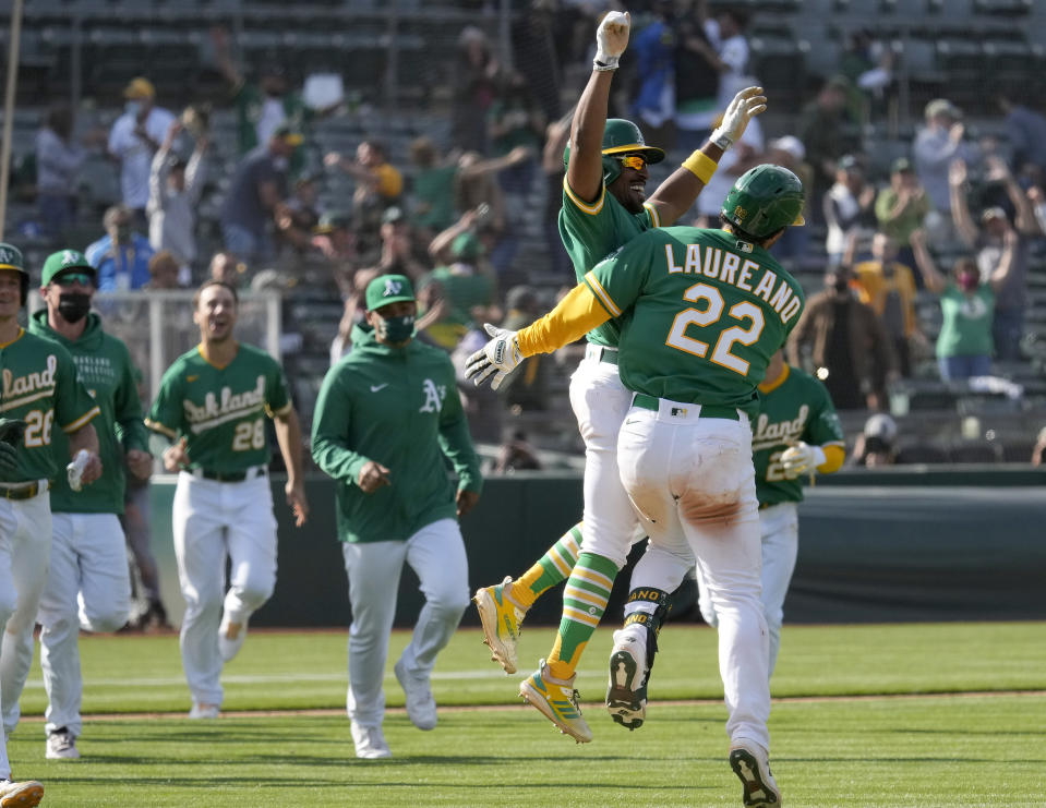 Oakland Athletics' Ramon Laureano (22) celebrates with Tony Kemp (5) and teammates after two runs scored on a throwing error by Minnesota Twins third baseman Luis Arraez during the 10th inning of a baseball game Wednesday, April 21, 2021, in Oakland, Calif. Laureano safe at first. Oakland won 13-12. (AP Photo/Tony Avelar)