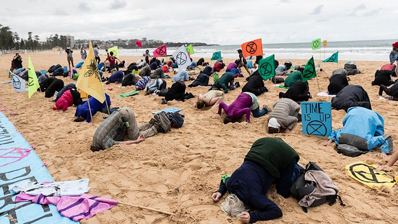 "Activists stick their heads in the sand at Manly Beach as part of the Extinction Rebellion's ""Week of Action"". Source: Getty Images."