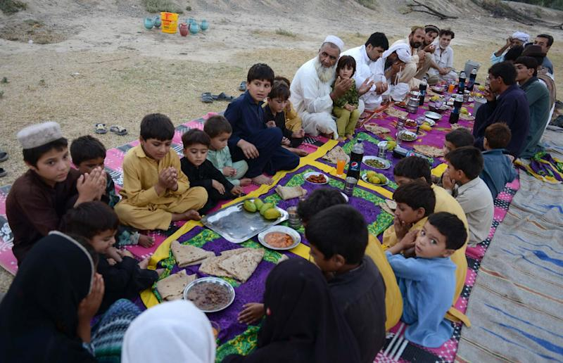 Gulzar Khan, who fled with his family following a military operation against militants in the North Waziristan tribal agency, prays alongside relatives before they break their Ramadan fast in Bannu on July 11, 2014 (AFP Photo/A Majeed)
