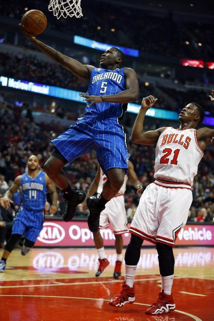 Orlando Magic shooting guard Victor Oladipo (5) goes in for a layup past Chicago Bulls shooting guard Jimmy Butler (21) during the first half of an NBA basketball game in Chicago on Monday, Dec. 16, 2013. (AP Photo/Jeff Haynes)