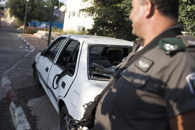 """GESHER-HAZIV, ISRAEL - AUGUST 22: A Policeman stands next to a car believed to have been damaged by the fallout of an """"Iron Dome"""" interceptor rocket after intercepting one of four rockets fired at Israel from Lebanon on August 22, 2013 in Kibbutz Gesher Haziv, Israel. According to an Israeli military spokesman, four rockets were fired toward northern Israel from southern Lebanon but none landed in Israel's territory. No-one was reported to have been injured but some light damage to a street and vehicle was believed to have been caused by the debris from Israel's rocket defence system. (Photo by Ilia Yefimovich/Getty Images)"""