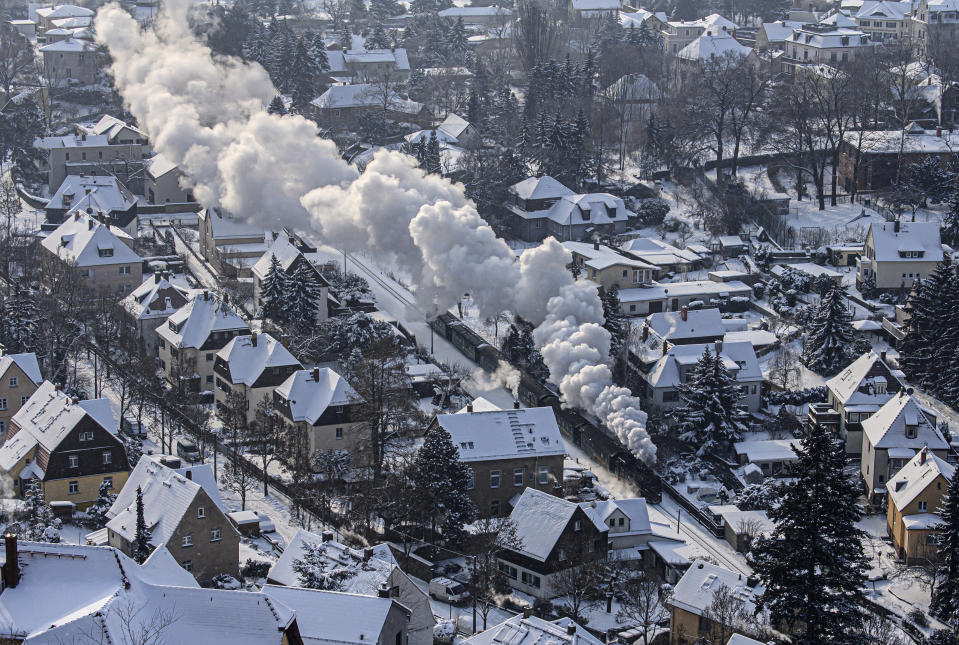 "The Lößnitzgrundbahn runs through a snowy winter landscape in Radebeul, Germany on Wednesday, Feb.10, 2021. The narrow-gauge railway, popularly known as the ""Lößnitzdackel"" or ""Grundwurm"", has a gauge of 750 millimetres and runs from Radebeul to Radeburg. (Robert Michael/dpa via AP)"