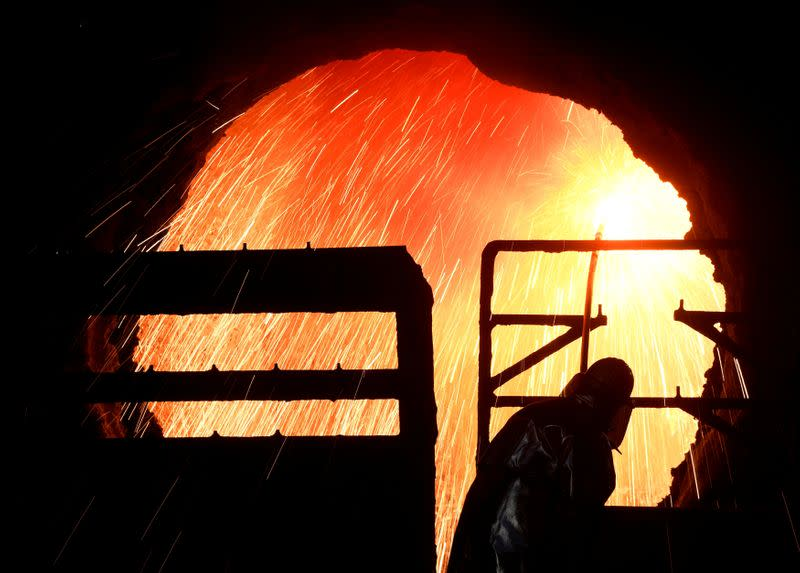 FILE PHOTO: A steelworker cleans a cylinder at the plant of German steel company Salzgitter AG in Salzgitter