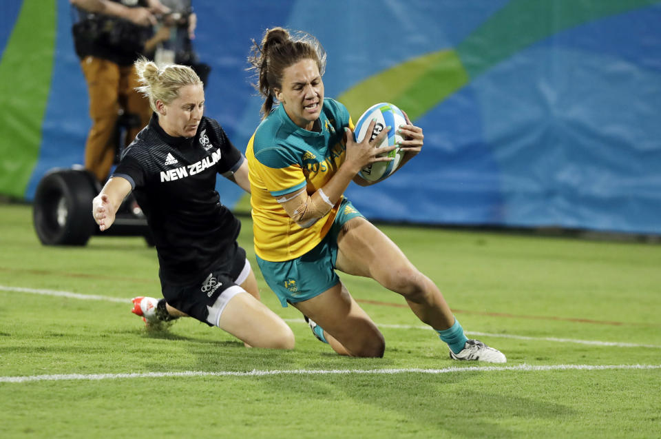 FILE - In this Aug. 8, 2016, file photo, Australia's Evania Pelite, right, scores a try as New Zealand's Kelly Brazier chases during the women's rugby sevens gold medal match at the Summer Olympics in Rio de Janeiro, Brazil. It was rugby in fast forward and it generated millions of new fans across the world. Rugby sevens made its Olympic debut in Rio de Janeiro in 2016 bringing all the usual hard-hitting tackles, collisions and swerving runs but leaving out the slow-mo elements of the traditional 15-a-side game. (AP Photo/Themba Hadebe, File)