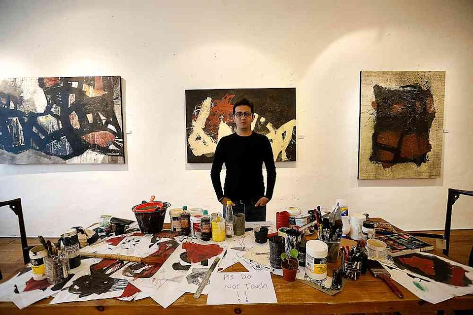 Syrian artist Alaa Shasheet with the installation piece that depicts his studio. — Picture by Sayuti Zainudin