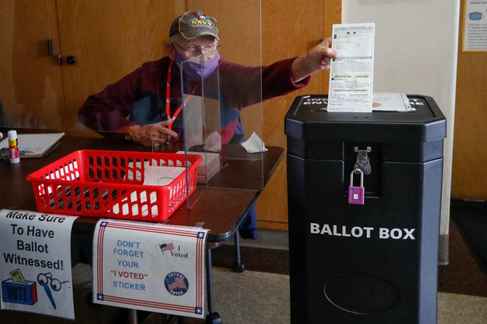 """<div class=""""inline-image__caption""""><p>An election worker drops a voter's completed ballot into a ballot box inside City Hall on the first day of in-person early voting for the November 3rd elections in Kenosha, Wisconsin, on October 20, 2020.</p></div> <div class=""""inline-image__credit"""">KAMIL KRZACZYNSKI/AFP via Getty Images</div>"""