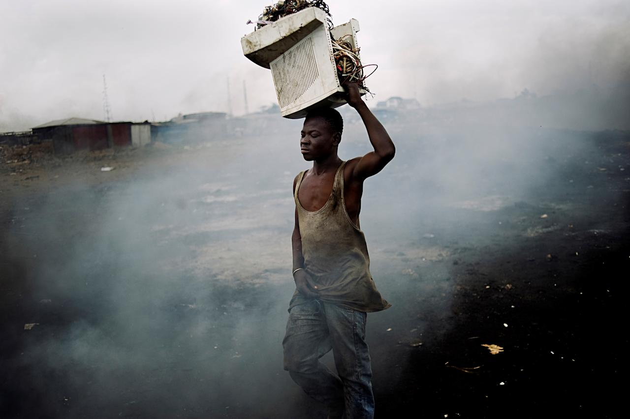 'E-Waste in Ghana' by Kai Löeffelbein. This striking image shows a man with an old computer on his head in the middle of a waste dump. Up to 50m tonnes of toxic electronic waste accumulate annually in the world and many are exported from developed countries to developing nations (Kai Löeffelbein)