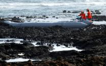Rescue workers search for bodies after a boat with 46 migrants from the Maghreb region capsized in the beach of Orzola