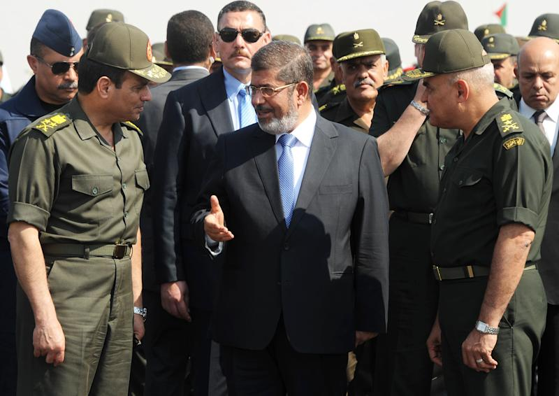 FILE - In this Wednesday, Oct. 10, 2012 file image released by the Egyptian Presidency, Egyptian President Mohammed Morsi, center, speaks with Minister of Defense, Lt. Gen. Abdel-Fattah el-Sissi, left, at a military base in Ismailia, Egypt. During his year as president, Morsi cultivated ties with Islamic radicals, making them a key support for his rule by pardoning dozens of jailed militants, restraining the military from an all-out offensive on jihadis in Sinai and giving their hard-line sheiks a platform to spread their rhetoric. Now with Morsi ousted and imprisoned, investigators are looking into possibly putting him on trial for links to jihadis, accusing him and his Muslim Brotherhood of being behind a wave of violence by Sinai-based militants in retaliation for the July 3 military coup that removed the Islamists from power, military and security officials say.(AP Photo/Egyptian Presidency, File)