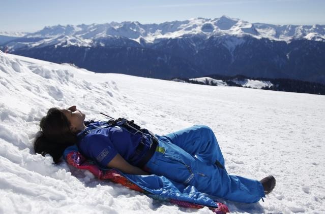 A volunteer enjoys a sunny afternoon on top of the mountain of Rosa Khutor during the 2014 Sochi Winter Olympics