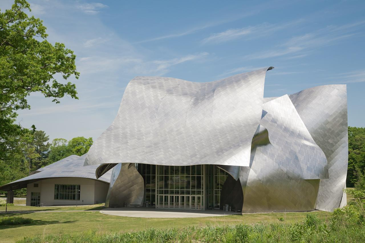 "Bard College tapped Frank Gehry to design its  Fisher Center Performing Arts, a 110,000-square-foot building with two theaters and four rehearsal studios. ""The front façade of the building can be interpreted as a theatrical mask that covers the raw face of the performance space,"" said the architect of the metallic sheets comprising the façade."