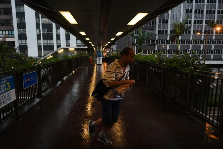 A man tries to walk against the wind from Typhoon Hato as Hong Kong's weather observatory raised the storm warning to the city's highest Typhoon 10 signal -- the first such alert in five years
