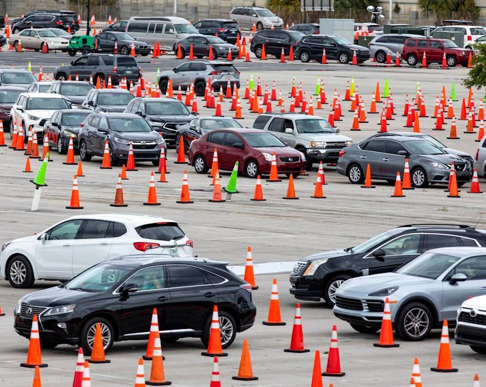 People line up in their cars to get vaccinated at Hard Rock Stadium in Miami Gardens, Florida, on Monday, April 12, 2021. The site will no longer require appointments and has expanded COVID vaccine hours.
