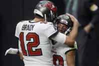 Tampa Bay Buccaneers quarterback Tom Brady (12) celebrates after making a touchdown pass to wide receiver Scott Miller, right, during the first half of an NFL football game, Sunday, Oct. 25, 2020, in Las Vegas. (AP Photo/Isaac Brekken)