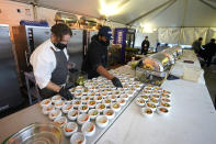 """Jason Wilson, left, a chef at The Lakehouse, a restaurant located in Bellevue, Wash., and sous chef Demetrius Parker, right, prepare dishes for the first course of a meal for diners in an outdoor tent set up on the turf at Lumen Field, Thursday, Feb. 18, 2021, in Seattle. Wilson and Parker were two of the chefs taking part in the inaugural night of the """"Field To Table"""" event at stadium, which is home to the Seattle Seahawks NFL football team. The event will feature several weeks of dates that offer four-course meals cooked by local chefs and served at tables socially distanced as a precaution against the COVID-19 pandemic. (AP Photo/Ted S. Warren)"""
