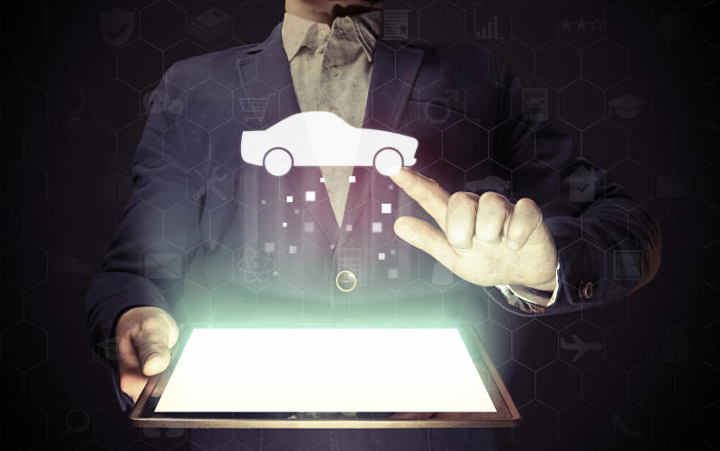 Man holding a lit-up tablet screen and pointing his left finger at a graphic of a vehicle hovering above it.