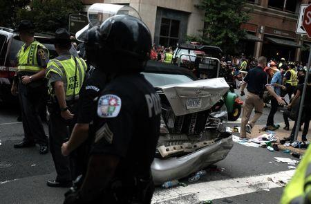 "First responders stand by a car that was struck when a car drove through a group of counter protesters at the ""Unite the Right"" rally Charlottesville"