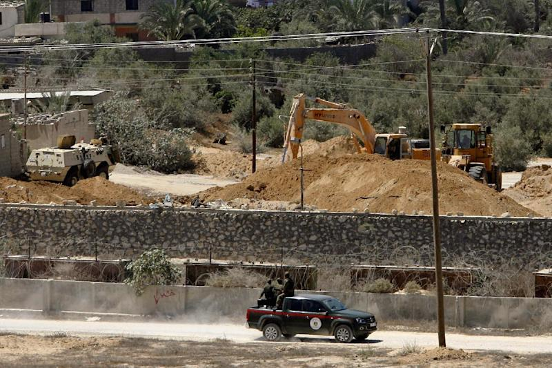 In this Wednesday, Aug. 22, 2012 photo, Palestinian Hamas border guards patrol the Egyptian Gaza border while an Egyptian bulldozer works on the demolition of a smuggling tunnel, as seen from Rafah, southern Gaza Strip. Hamas had hoped the Islamists who took charge in Egypt this summer -- fellow members of the region's Muslim Brotherhood -- would swiftly turn the shared border crossing into a free-flowing trade route, ending Gaza's five-year isolation from the world and making the tunnels obsolete. (AP Photo/Eyad Baba)