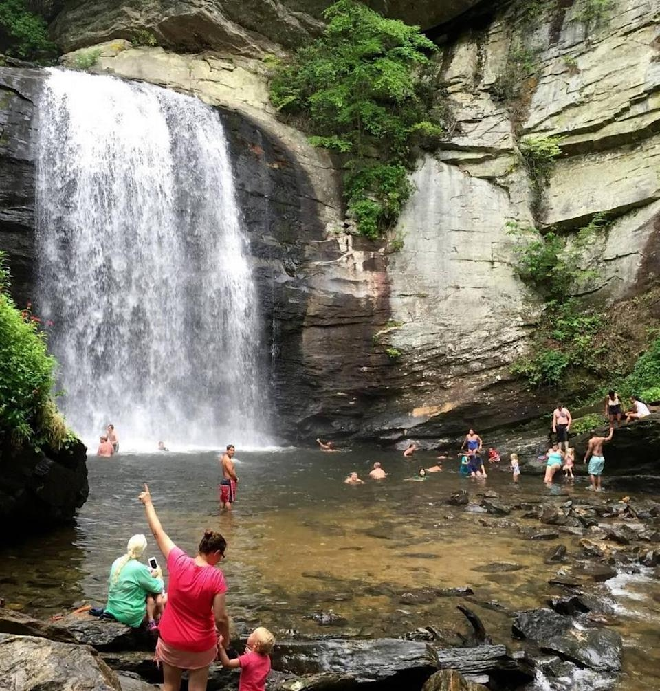 Visitors splash, swim and take photos on July 25, 2016, at the Looking Glass Falls in the Pisgah National Forest, west of Brevard, NC. The 60-foot falls is a popular stop for travelers, offering ample parking and easy steps that lead to two observation points and access to the swimming pool at its base.