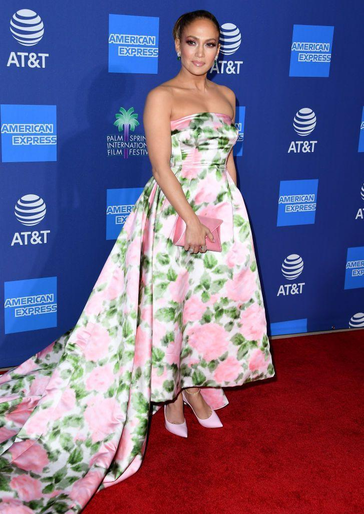 """<p>The 50 year-old star wore a Richard Quinn floral ballgown to pick up the Spotlight Award for her role in hit <a href=""""https://www.elle.com/uk/life-and-culture/a30177996/jennifer-lopez-reaction-to-fan-hustlers-plane/"""" rel=""""nofollow noopener"""" target=""""_blank"""" data-ylk=""""slk:Hustlers"""" class=""""link rapid-noclick-resp"""">Hustlers</a>. </p><p>Alongside her matching clutch and court heels the mother-of-two wore her hair in a large bun that totally reminded us of her character's iconic hairdo' in <a href=""""https://www.elle.com/uk/beauty/hair/a30387537/jennifer-lopez-hair-maid-in-manhattan/"""" rel=""""nofollow noopener"""" target=""""_blank"""" data-ylk=""""slk:Maid In Manhattan"""" class=""""link rapid-noclick-resp"""">Maid In Manhattan</a>. </p>"""