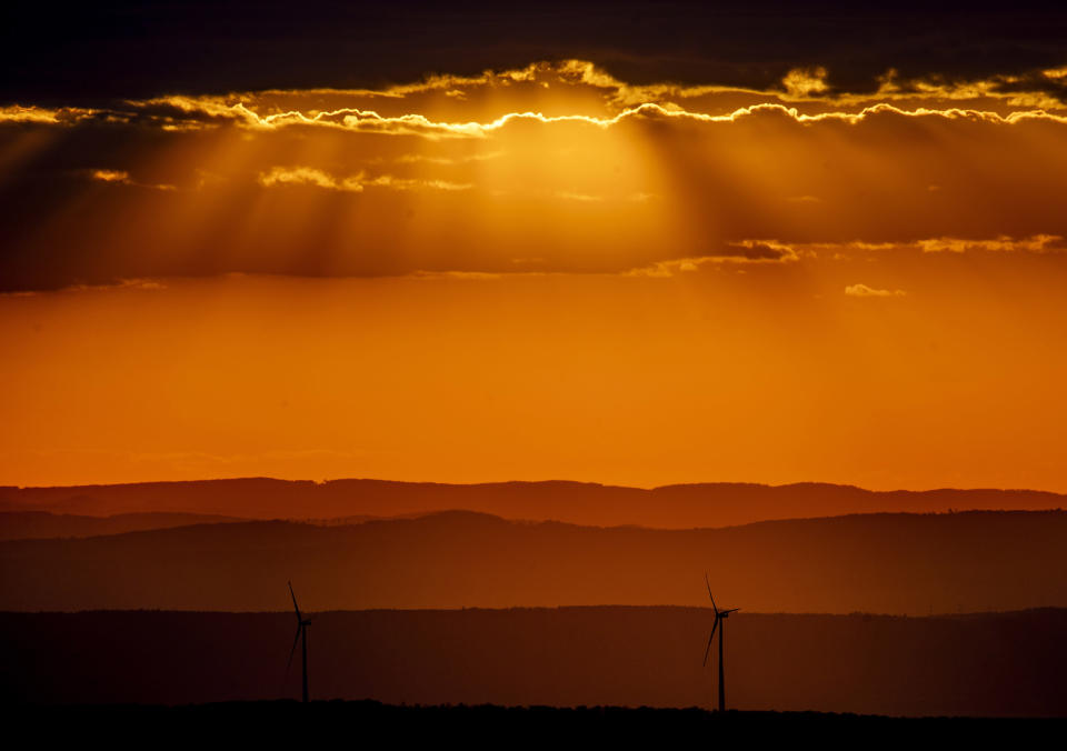 Wind turbines stand on a hill as sun rays fall through the clouds near Frankfurt, Germany, Tuesday, Aug. 25, 2020. (AP Photo/Michael Probst)