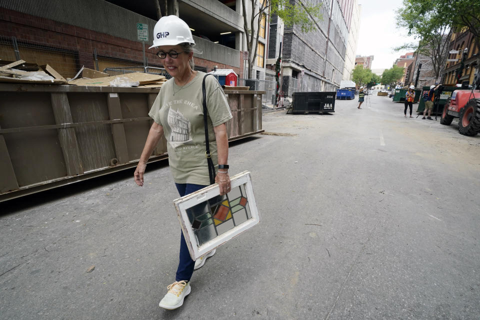 Betsy Williams carries a window she recovered from her apartment in a building damaged in a Dec. 25, 2020, suicide bombing Friday, June 25, 2021, in Nashville, Tenn. Six months after a Christmas Day bombing ripped a hole in historic downtown, workers continue to chip away at cleanup efforts so that revitalization can begin. The tediously slow process has meant workers haven't been able to access some of the buildings until recent weeks. (AP Photo/Mark Humphrey)