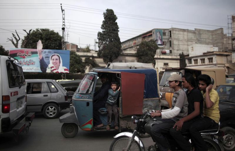 Backdropped by a banner showing Pakistan's slain leader Benazir Bhutto, motor vehicles are stopped during a traffic jam, in Rawalpindi, Pakistan, Saturday, March 16, 2013. Pakistan's government is passing a remarkable milestone in a country that has faced three military coups -- it's the first democratically elected body to finish its term. But after years of militant attacks, worsening electricity blackouts and faltering economic growth, the political party that took office five years ago on a wave of sympathy following the assassination of iconic leader Benazir Bhutto will likely find it more difficult this time to win voters to its side. (AP Photo/Nathalie Bardou)