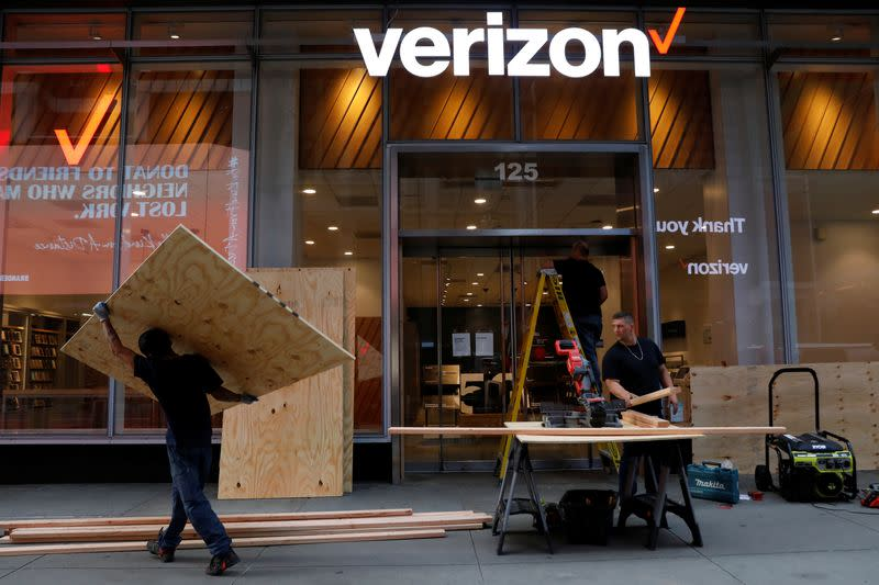 Workers board up a Verizon store in midtown Manhattan during protests against the death in Minneapolis police custody of George Floyd, in New York